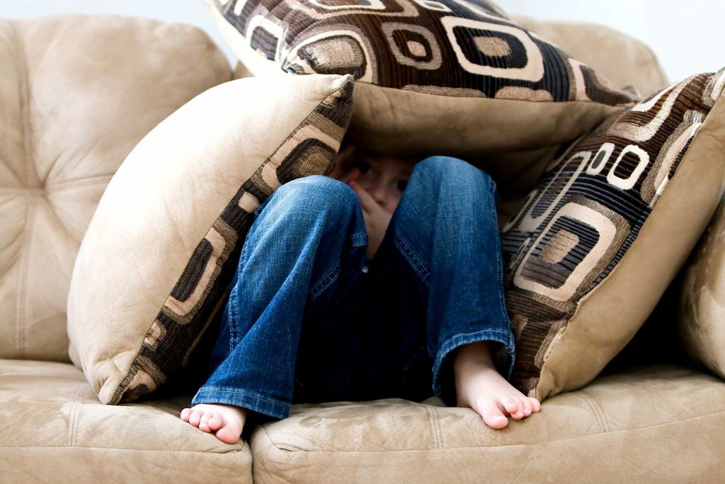 A child hides under couch cushions