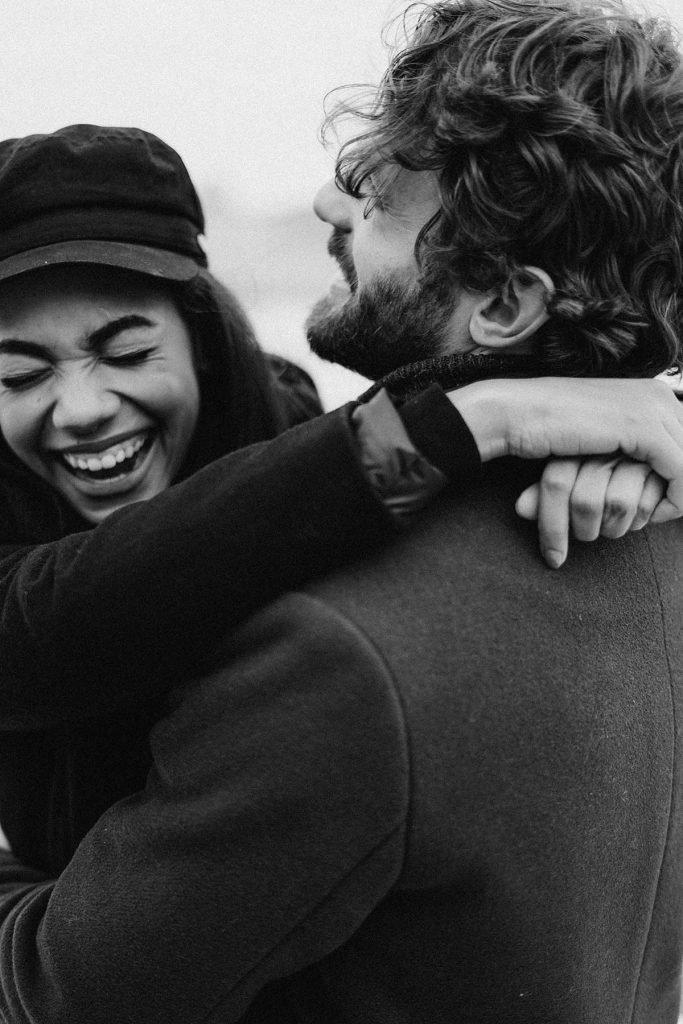 A man and woman hug and laugh together