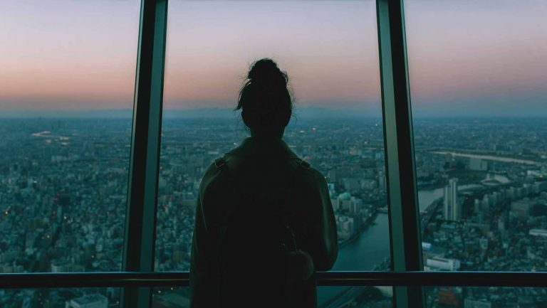 A young woman looks out over a city
