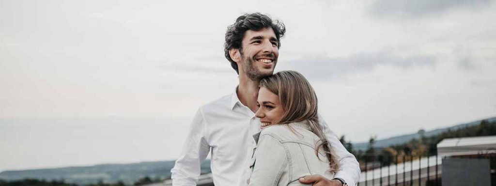 A young couple hug and smile